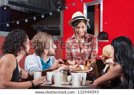 Cute Asian woman serving pizza to diners outside