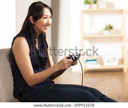 Cute Asian young woman having fun with game controller in a living room. - stock photo