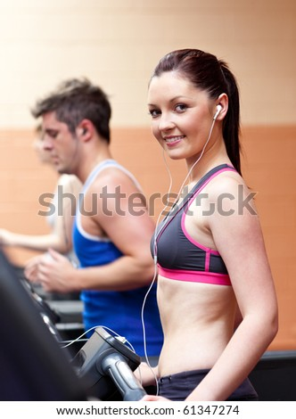 Cute athletic woman standing on a running machine with earphones in a fitness center - stock photo
