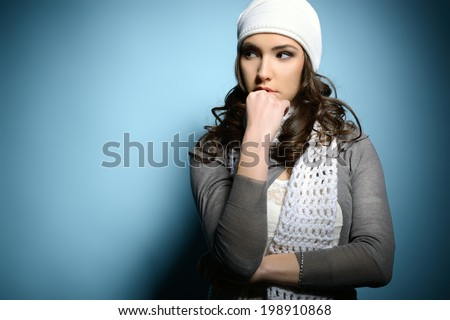 Cute attractive fashion young girl in warm clothes looking left at copyspace, over blue - stock photo