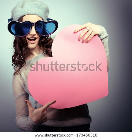 Cute attractive fashion young girl posing with funny big love glasses and pointing at pink heart, toned - stock photo