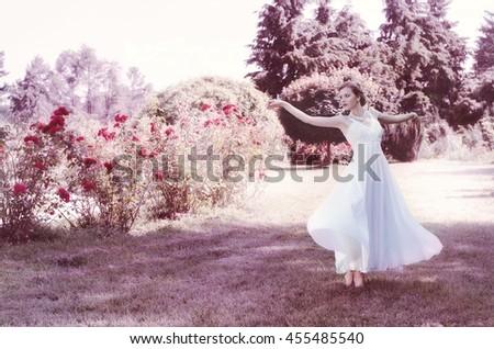 cute, attractive, gentle, romantic, sensual girl in a romantic hairstyle, wearing a white dress. She dances in the lush garden. Bride. Ballerina dancer. - stock photo