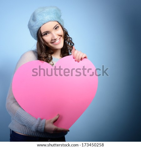 Cute attractive girl posing with big pink heart over blue background. Holiday