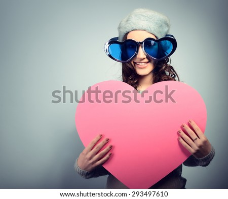 Cute attractive girl posing with big pink heart over blue background. Holiday - stock photo