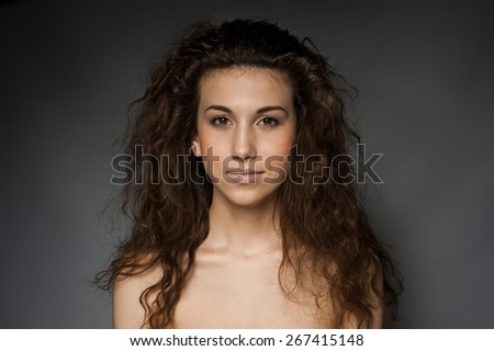 Cute, attractive girl with curly hair on gray background - stock photo