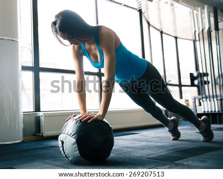 Cute attractive young woman working out with fit ball at gym