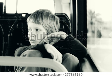 Cute autistic boy siting in empty bus - stock photo
