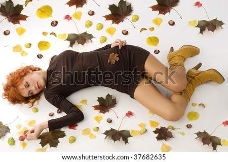 cute autumn girl in brown dress and yellow boots laying down between leaves