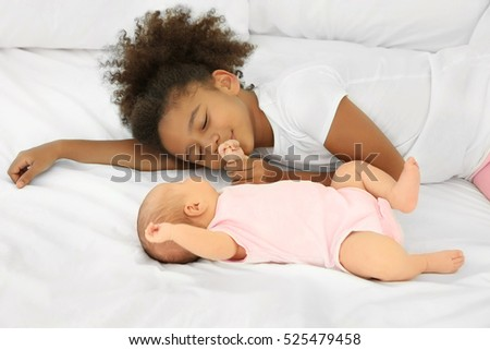 Cute baby and elder sister on bed