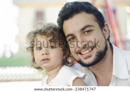 Cute baby and father posing in outdoors image in city.