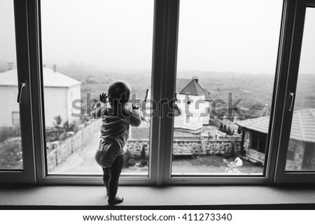 Cute baby at home in white room stands near window - stock photo