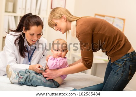 Cute baby being examine by pediatrician with stethoscope mother assistance - stock photo