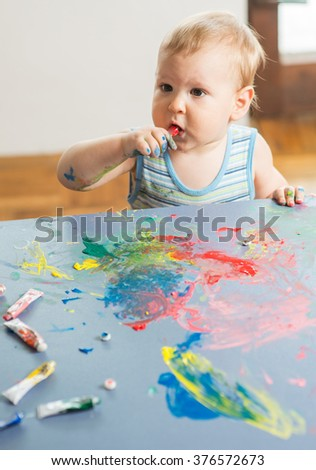Cute baby boy artist playing with colors