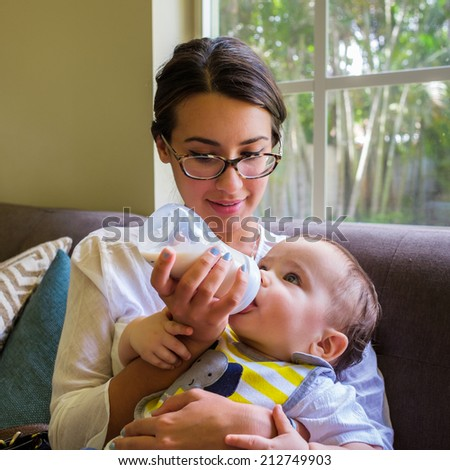 Cute baby boy being fed milk by a pretty young woman in a home setting.
