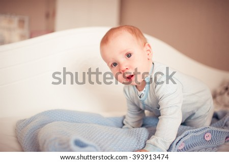 Cute baby boy crawling in bed. Wake up. Looking at camera. Childhood.