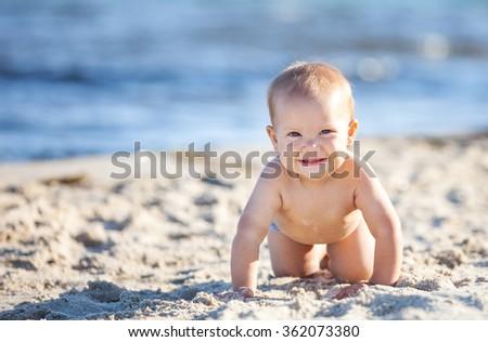 Cute baby boy crawling on beach - stock photo