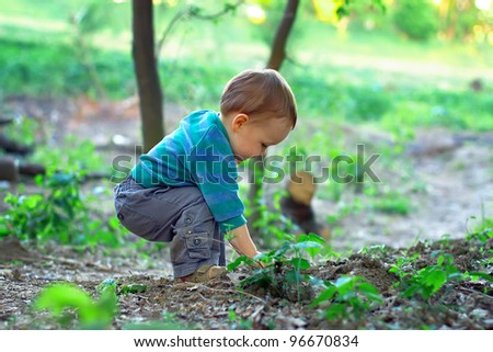 cute baby boy digging in ground in spring forest - stock photo
