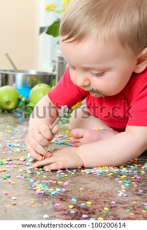 Cute baby boy eating cake decorations on counter top - stock photo