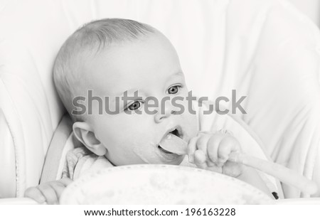 cute baby boy eating on her own with big spoon on a white background ( black and white )