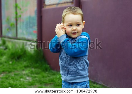 cute baby boy emulate talking on the phone, while playing outdoor - stock photo