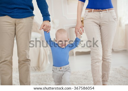 Cute baby boy holding father and mother by the hand and takes first steps - stock photo