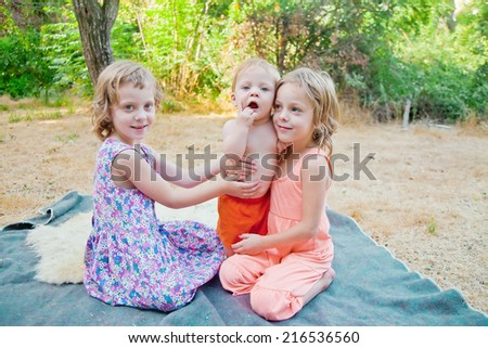Cute baby boy in a park with his two sisters at sunset - stock photo