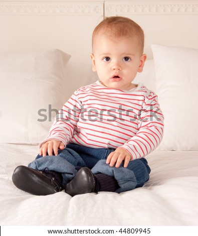 Cute baby boy in jeans and striped t-shirt sitting on a bed - stock photo