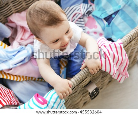 Cute baby boy in wicker basket with clothes - stock photo