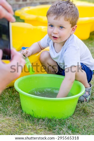 Cute baby boy is playing with water and posing in front of smartphone in the garden - stock photo