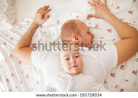 Cute baby boy is relaxing on the back of his father - stock photo