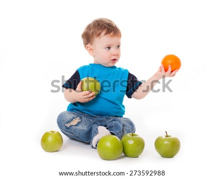 Cute baby boy kid eating and playing with green apples and orange  isolated on white background - stock photo