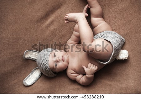 Cute baby boy lie on a beige background wearing a crochet hat in the form of a Christmas bunny with ears and tail - stock photo