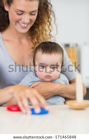 Cute baby boy looking at mother playing with toys - stock photo
