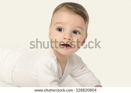 Cute baby boy looking surprised. Adorable baby crawling looking curious isolated on white. Baby lying on his tummy. - stock photo