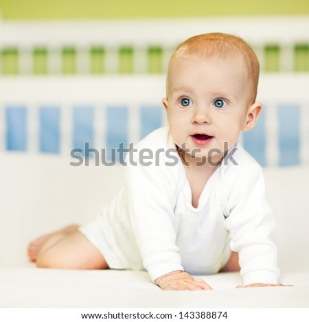 Cute baby boy looking surprisedly at something. - stock photo
