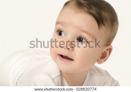Cute baby boy looking to the side. Adorable baby crawling looking curious isolated on white. Baby lying on his tummy. - stock photo