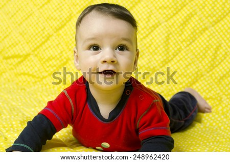Cute baby boy looking up curious. Baby lying on his tummy smiling and looking up. - stock photo