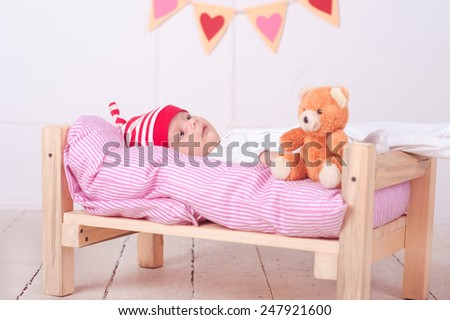 Cute baby boy lying in bed with teddy bear and valentines heart at background. Bed time. Resting.  - stock photo