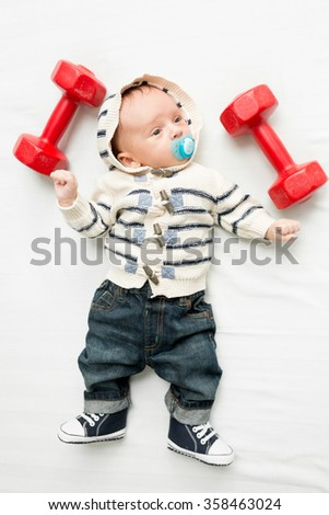 Cute baby boy lying on bed with dumbbells - stock photo