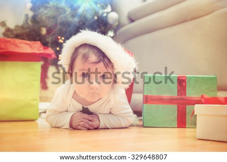 Cute baby boy lying on floor at christmas at home in the living room