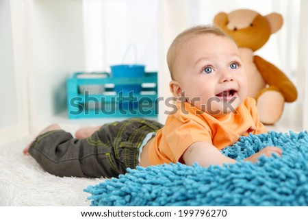 Cute baby boy lying on floor in room