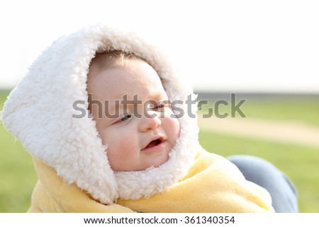 Cute baby boy 7 months of age outdoors on a cold afternoon. - stock photo
