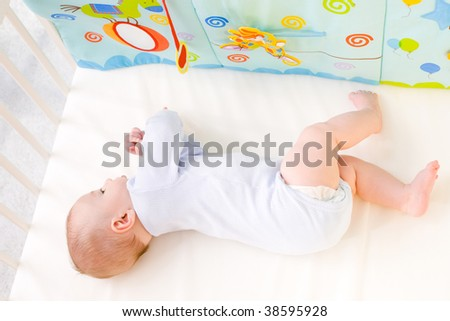 Cute baby boy (4 months old) lying on back in baby bed. - stock photo