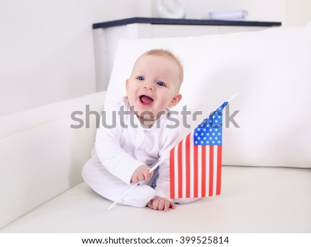 Cute baby boy on white couch with American flag, closeup - stock photo