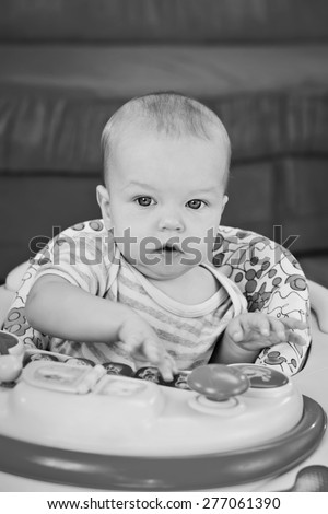 cute baby boy playing at home and looking at the camera ( black and white ) - stock photo