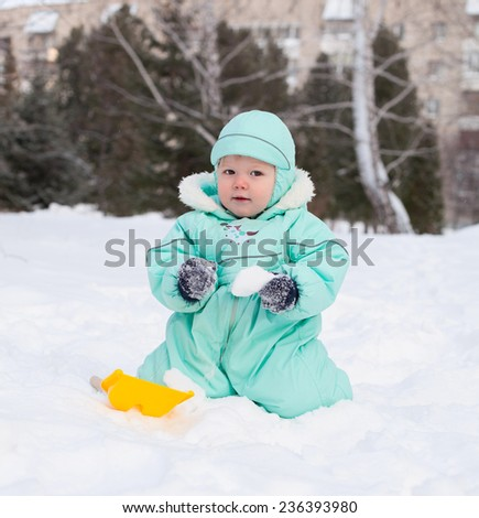 Cute baby boy playing in park in winter, holding snow in hands - stock photo