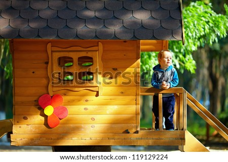 cute baby boy playing in tree house, sunny outdoor - stock photo
