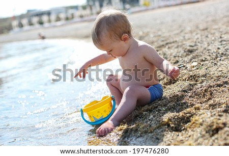 cute baby boy playing on the beach with water - stock photo
