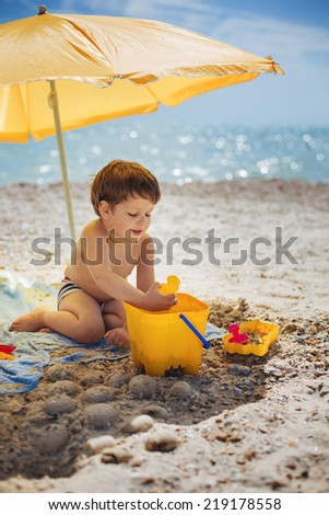Cute baby boy playing with beach toys on tropical beach - stock photo