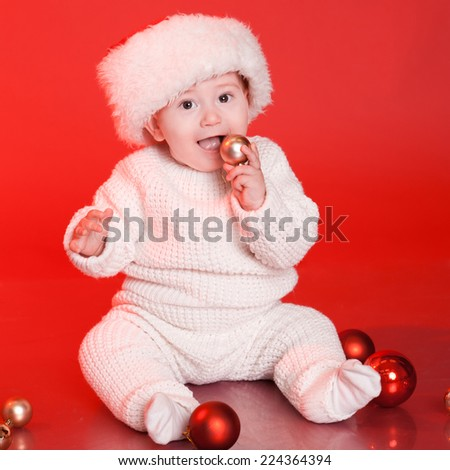 Cute baby boy playing with christmas decorations. Wearing knitted winter clothes over red - stock photo